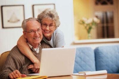 Seniors on laptop managing their wealth
